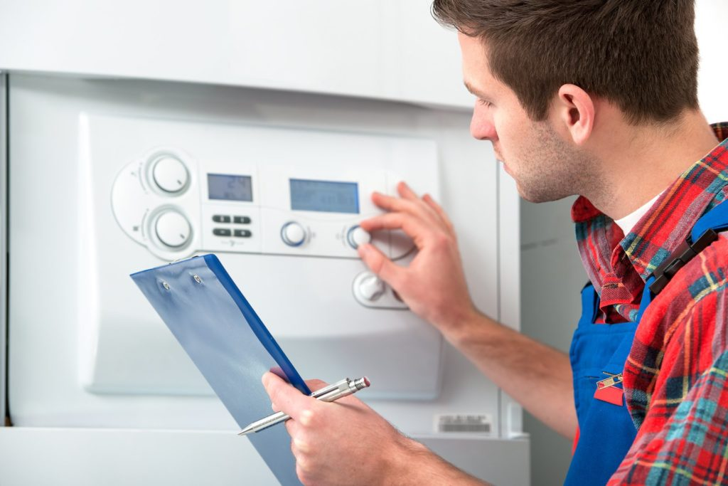 Technician servicing the gas boiler for hot water and heating ** Note: Shallow depth of field